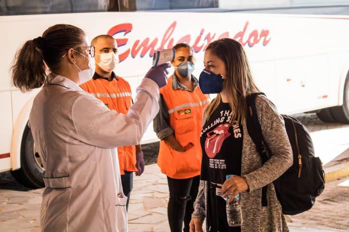 Voluntários verificam a temperatura dos passageiros que chegam à Rodoviária de Pelotas